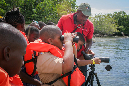 """Do you see the Pelican?"" Damian Whyte, environmental officer of the Urban Development Corporation, Jamaica, seems to be asking students of Swallowfield Primary School as he demonstrates how to use the telescope as a part of the Caribbean Waterbird Census 2016 in Palisadoes Port Royal Protected Area. The equipment was donated to NEPA and Jamaica Environment Trust by BirdsCaribbean (photo courtesy of Ava Tomlinson)."