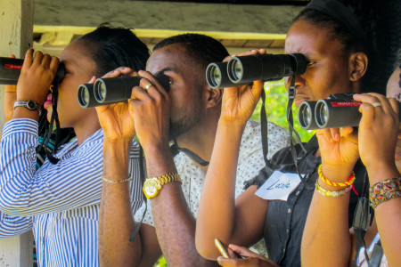 Teachers train their binoculars, looking from the verandah of Seville Great House.