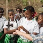 A child releases a banded bird at Belmont Estates in Grenada. Adults and children learned about how birds are captured and banded for research, as well as how to use binoculars and identify birds in birding walks. (Photo courtesy of Belmont Estates).