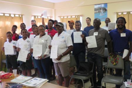 Workshop participants proudly show their signed pledge to help protect Grenadines' seabirds. (photo by Julianna Coffey)