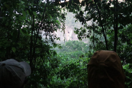 John Zeiger (left) and Justin Proctor (right) stand firm against the rain and mosquitos during an evening observation session of Ram Goat Cave (black spot in center of photo). (Photo by Seth Inman)