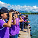 Students from the Jose Horacio Cora School, Arroyo, Puerto Rico, were delighted to learn how to use binoculars to spot Magnificent Frigatebirds, Royal Terns, and Osprey  feeding in the waters at the Jobos Bay National Estuarine Research Reserve. (Photo by Ernesto Olivares)