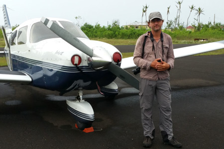 Eric Delcroix, avid birder from Guadeloupe and Frantz's husband, stands in front of the Piper PA28 airplane before take-off (Photo by Anthony Levesque)